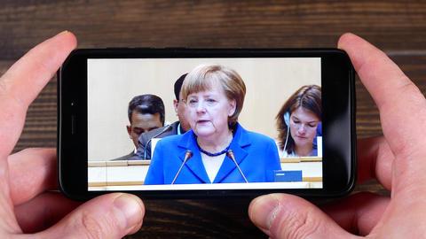 Ternopil, Ukraine - February 19, 2018: looks at the Angela Merkel on smartphone Archivo