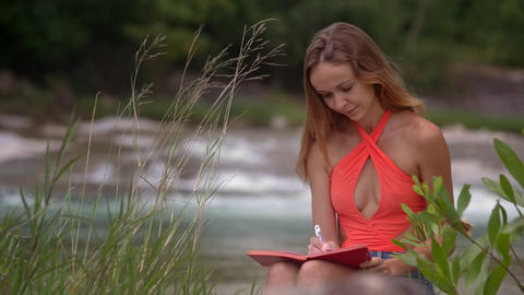 Wind Shakes Hair Girl Writes in Notebook at River Footage