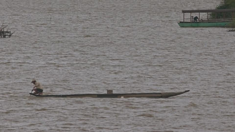 Dugout Canoe with Man Sails on Lake Past Big Boat Footage