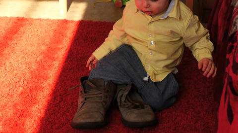 cute 1 year old baby trying get up with adult boots Footage