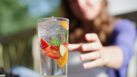 A shot of a lady reaching for a fruity summer cocktail in slow motion Live Action
