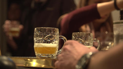 A shot of glasses of beer being passed over the bar in a pub Live Action