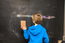Back view of a little boy cleaning chalkboard Photo