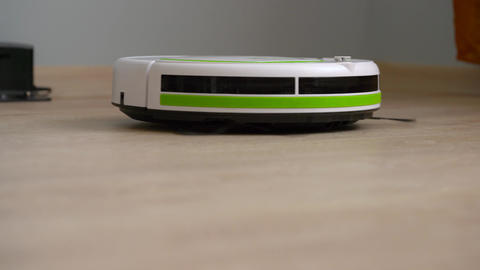 Vacuum cleaner robot that cleans a wooden floor Footage