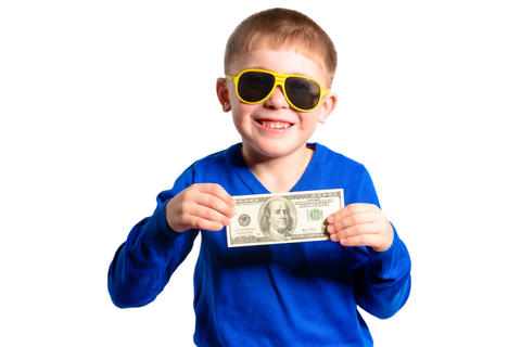 A little boy in a blue sweater smiles and holds a hundred dollars Fotografía
