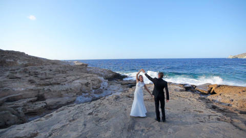bride and groom dance on the seashore in their wedding day Image