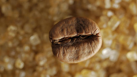Brown coffee bean on sweet brown sugar crystals, macro shot Stock Video Footage