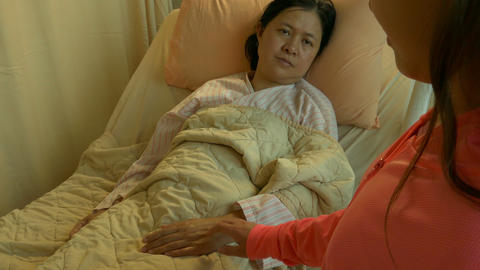 Daughter holds ill mother's hand in hospital bed OTS Live影片