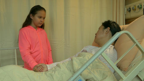 Daughter holds mother's hand in hospital bed Live影片
