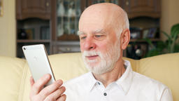 Senior man at home using cellphone having video chat. Professor talking on Footage