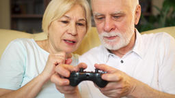 Senior couple gamers playing video games at home. Players with remote controller Footage
