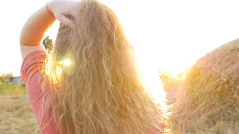A beautiful girl at the sunset adjusts her hair. Slow motion. A stack of hay Footage
