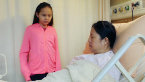 Daughter stands by sick mother's bed in hospital bed rack focus Live影片