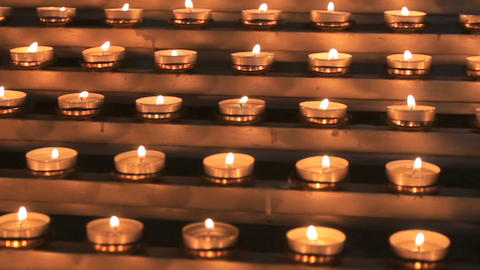 Many small church candles burn at the altar Footage