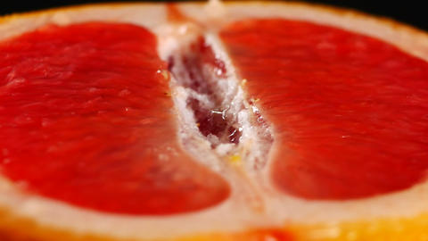 Half of grapefruit, rotating on a black background Live Action