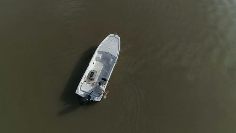 Man in a boat clonkfishing. Drone shot from above Footage