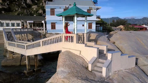Woman in Red Sits on Handrails on Rocks Upper View Footage