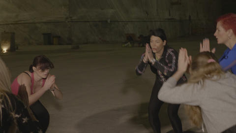 Group of people stretching and doing pilates in a cold underground place made of Footage