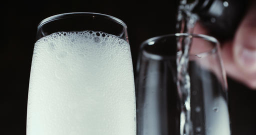 Glasses with champagne bubbles on dark background Footage