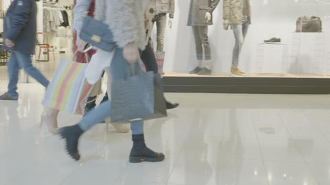 Casual weekend day at the mall where people walk with shopping bags in their Footage