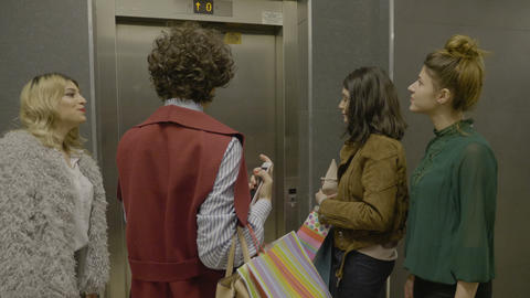 Group of female managers friends holding shopping bags and using elevator to Footage