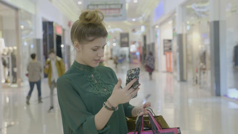 Stylish teenage girl carrying shopping bags while holding smartphone in her hand Footage