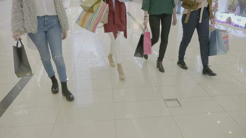 Low shot of group of female legs walking in the mall lobby while carrying Footage