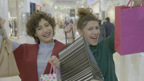 Young female entrepreneurs expressing their happiness by showing shopping bags Footage