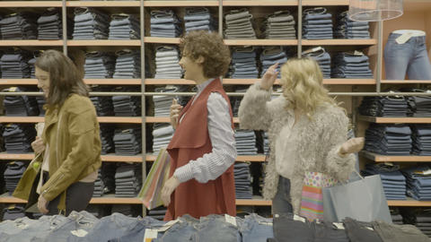 Young attractive female models having fun while shopping and looking at a pair Footage