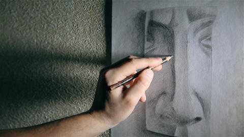 Man artist draws a nose with a graphite pencil Footage