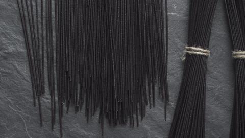 Black rice vermicelli on a stone top view. Asian cuisine. Video desaturate Archivo