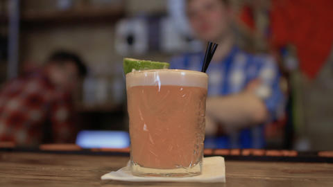 Barman presents exotic cocktail decorated with a lime Stock Video Footage