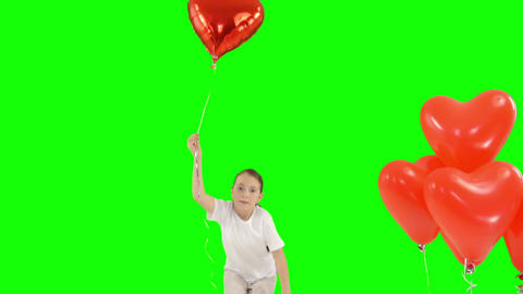 Little girl holding bundle of red heart shaped air balloons. Bounces up Footage
