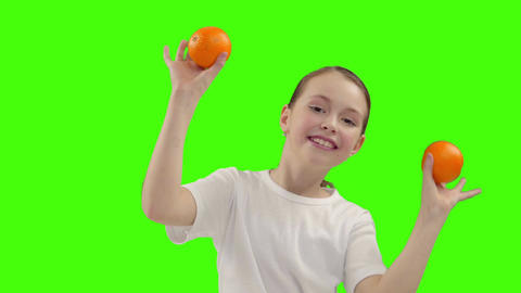 Happy girl holds half of orange near the face Live Action
