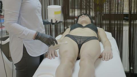 Beautician woman applying moisturizing body lotion on beauty female legs in spa Footage