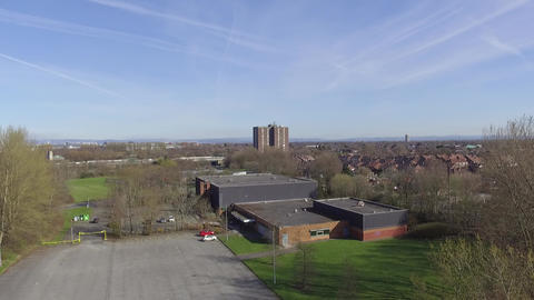 Flying Backwards Away from Sports Centre Over Urban Park Footage