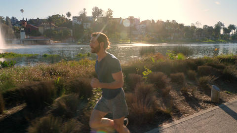 Athletic Man Jogging Around A Small Lake Footage