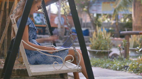 Lady in Blue Sits and Holds Modern Laptop on Swing Footage