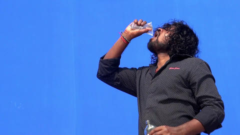 Young man drinking water and drink on blue screen background Footage