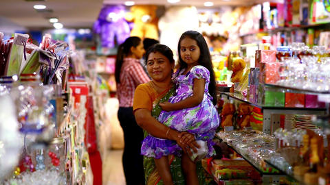 beautiful young girl and grandmother searching a gift at shopping mall Live Action