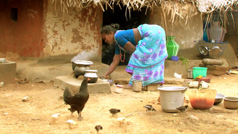 An unidentified Indian woman cooking food in traditional Indian style in village Live Action
