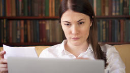 Businesswoman at home working with documents on laptop. Home-office concept Footage