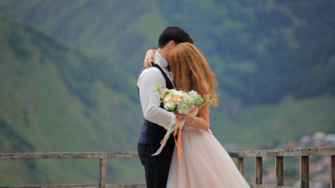 Wedding day. Groom and bride against the background of mountains GIF
