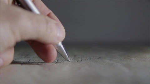 A man with a ballpoint pen writes something on white paper Footage