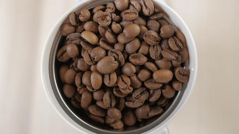 Coffee beans poured. Roasted coffee beans poured into a coffee grinder. Close-up Footage
