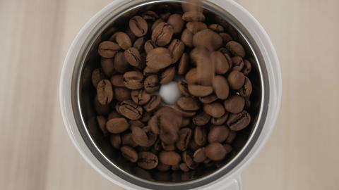 Coffee beans poured. Roasted coffee beans poured into a coffee grinder. Close-up Live Action
