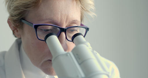 Female scientist looking through microscope Footage