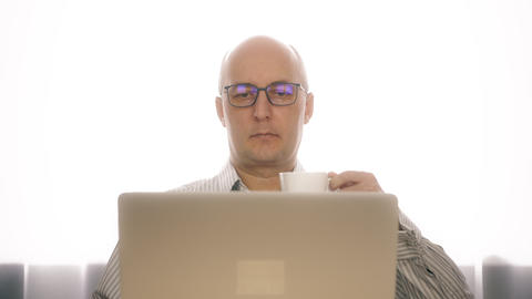 Adult man working on notebook and drinking coffee from cup in home office Live Action
