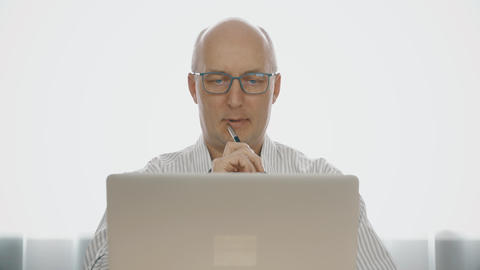 Pensive man looking on notebook screen during work in home studio Live Action