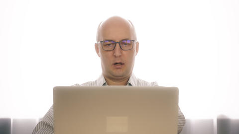Adult business man in glasses working on laptop in home office interior Footage